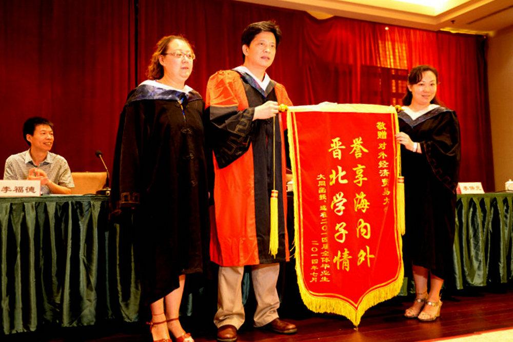 2014届毕业生代表向对外经济贸易大学赠送了锦旗.